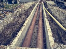 Metal pipes layed into concrete trench outdoor. stock photography