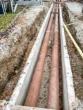 Metal pipes layed into concrete trench outdoor. stock photos