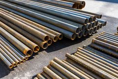 Metal pipes stacked. In a warehouse on asphalt stock image