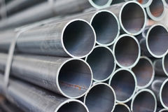Metal pipes in a warehouse. Stacks of new round steel pipe stock photo