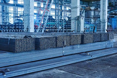 Metal pipes in a warehouse. Stacks of new square steel pipe Stock Photos