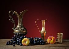 Metal pitcher and fruit Stock Photos