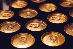 Metal piwnych puszek tła czerni złoto fotografia stock