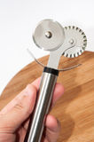Metal pizza cutter in the hand Stock Images