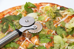Metal pizza round cutter on the pizza with letuce.  Royalty Free Stock Photography