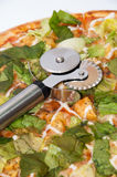 Metal pizza round cutter on the pizza with letuce.  Stock Image