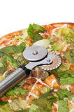 Metal pizza round cutter on the pizza with letuce.  Stock Photo