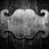Metal plaque on black wood Stock Images