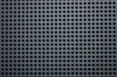 Metal plate as background. Black, metallic sheet with holes Stock Image