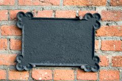 Metal plate on brick wall. An old metal plate, ornament, copy space, blank, includes work path around the plate Royalty Free Stock Images