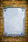 Metal plate on brick wall Stock Photos