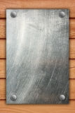 Metal plate on brown wooden background. Royalty Free Stock Photo