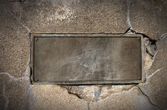 Metal Plate on Concrete Wall. Old metal plate with bolts on cracked concrete wall Royalty Free Stock Photos
