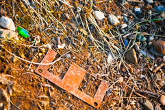 Metal plate on the ground. A metal plate on the sand is like a letter `E Royalty Free Stock Images