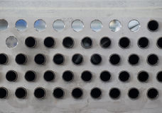 Metal plate with holes and pipes. Part of an industrial air-cooled condenser under production Stock Images
