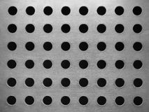 Metal plate with many circular holes. Background Stock Photography
