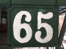 Metal plate numbered 65 in white Stock Image