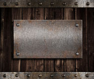Metal plate  on old wooden wall Royalty Free Stock Images