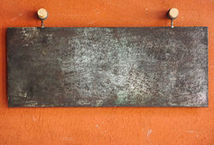 Metal plate on orange wall Stock Images