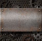 Metal plate over rusty gears background. Old metal plate over rusty gears background Stock Photography