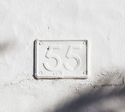 Metal plate painted with wall paint showing number 55 Royalty Free Stock Images