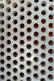 Metal Plate with Round Holes. A metal surface with round holes and some sand on it Royalty Free Stock Images