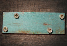 Metal plate screwed on dark brown wooden board Royalty Free Stock Photo