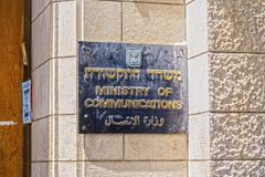 Metal plate signage of Israeli Ministry of Communications in Hebrew, English and Arabic. Jerusalem, Israel - June 16, 2018: Metal plate signage of Israeli royalty free stock photo