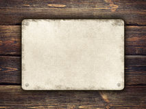 Metal plate on wooden background Royalty Free Stock Photo