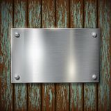 Metal plate on a wooden wall Royalty Free Stock Photography