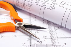 Metal pliers and rolled electrical diagram on construction drawing of house Stock Photography