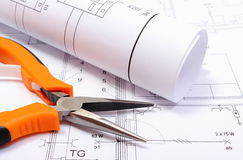 Metal pliers and rolled electrical diagram on construction drawing of house Stock Photo
