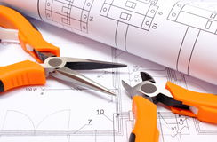 Metal pliers and rolled electrical diagram on construction drawing of house Royalty Free Stock Image