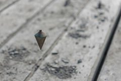 Metal plumb line used in construction site. Old metal plumb line used in construction site Royalty Free Stock Image