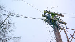 Metal, polo eléctrico de madera, líneas eléctricas pilón, instalaciones del poder, mala ensambladura del alambre Imagen de archivo libre de regalías