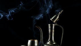 Metal pot and cup with moroccan tea and smoke at black bacground. Metal pot and cup with moroccan tea and smoke at black background with brown shugar nearby stock video footage