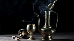 Metal pot and cup with moroccan tea and smoke at black bacground stock footage