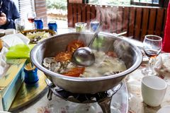 A metal pot of fish soup is on the table on the gas hob. Hot soup, goes steam, pieces of fish and tomatoes close-up. Delicious food, a trip to Asia royalty free stock image