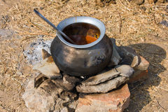 Metal  pot with food on fire, India Royalty Free Stock Photography