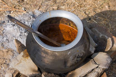 Metal  pot with food on fire, India Royalty Free Stock Images