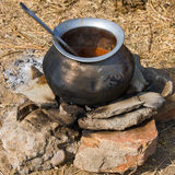 Metal  pot with food on fire, India Royalty Free Stock Image