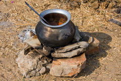 Metal  pot with food on fire, India Stock Photo