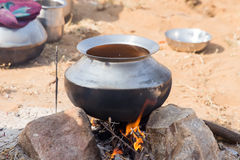 Metal pot with food on fire Royalty Free Stock Image
