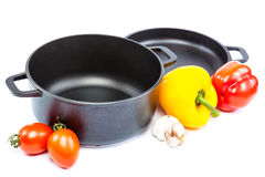 Metal pots and pans with vegetables. Stock Photos