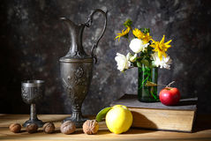 Metal pottery with various fruits and books Royalty Free Stock Photography