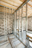 Metal profile frame for plasterboard walls and pipes with valves of a heating system in the house. Metal profile frame for plasterboard walls and pipes with stock photo
