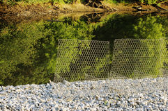 Metal protective mesh near the canal with water protects the shedding of gravel roads Stock Images