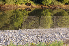 Metal protective mesh near the canal with water protects the shedding of gravel roads Royalty Free Stock Photo
