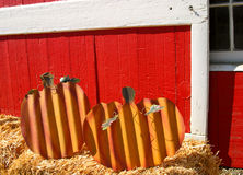 Metal Pumpkin Patch. Metal pumpkins sit on haystacks in front of a red barn at a pumpkin patch and harvest festival in Ventura County, California Royalty Free Stock Photos