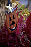 Metal Pumpkin Yard Decoration with Big Goofy White Teeth and Witch's Hat Lurks in Purple Plants Royalty Free Stock Images